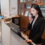 Welcome to the hotel,Happy young Asian woman hotel receptionist worker smiling standing,she taking  telephone call at a Modern luxury reception counter waiting for guests getting key card in hotel