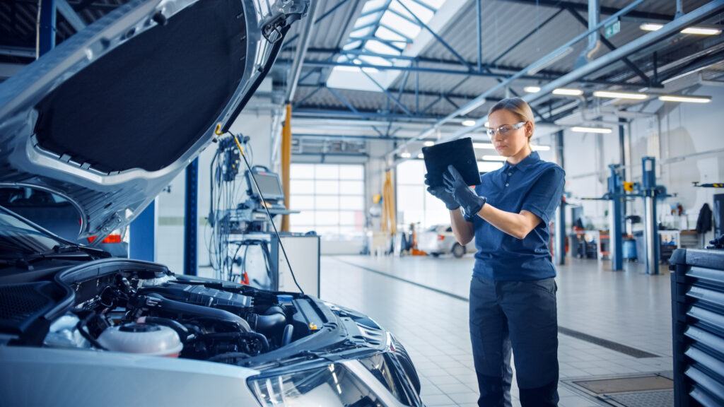 Female Mechanic Uses a Tablet Computer with an Augmented Reality Diagnostics Software. Specialist Inspecting the Car in Order to Find Broken Components Inside the Engine Bay. Modern Car Service.